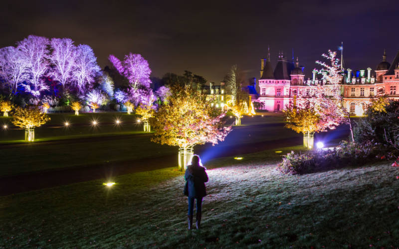 Visitor stands in front of Christmas illuminated Waddesdon Manor