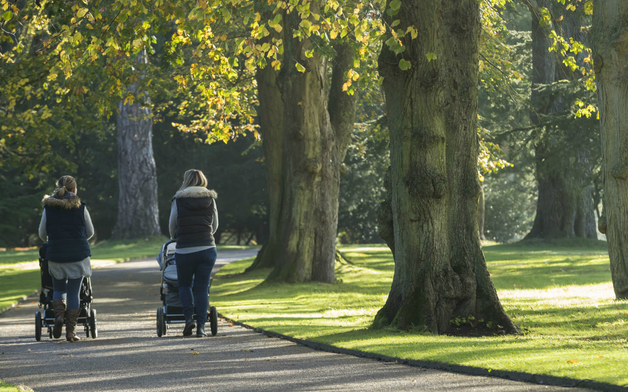 Two mothers walking with buggies in the grounds at Waddesdon