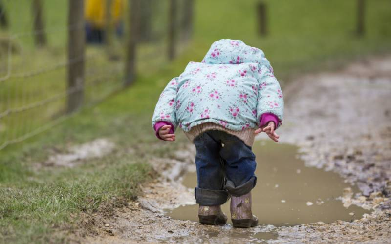 Little girl wearing wellies splashing in muddy puddles