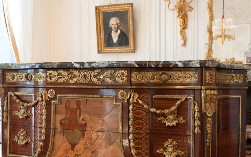 Riesener chest of drawers in Waddesdon Manor with portrait of Riesener on wall behind