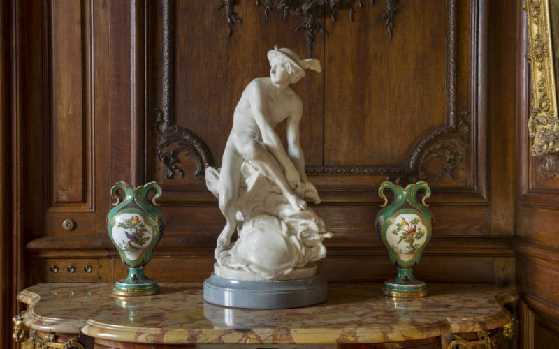 Small male statue upon a marble table with a green vase on either side
