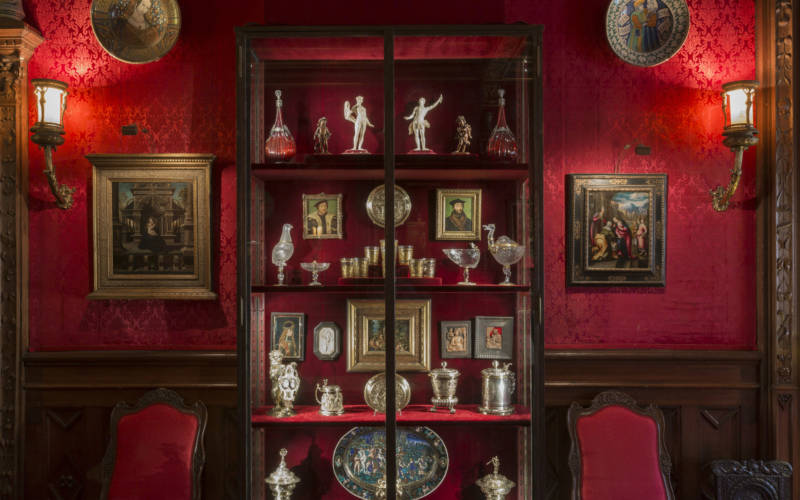 Tall glass cabinet containing porcelain figurines, glass goblets and silver tankards