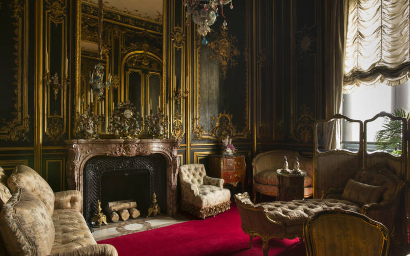 An ornate clock upon a fireplace, surrounded by antique sofas on a red carpet