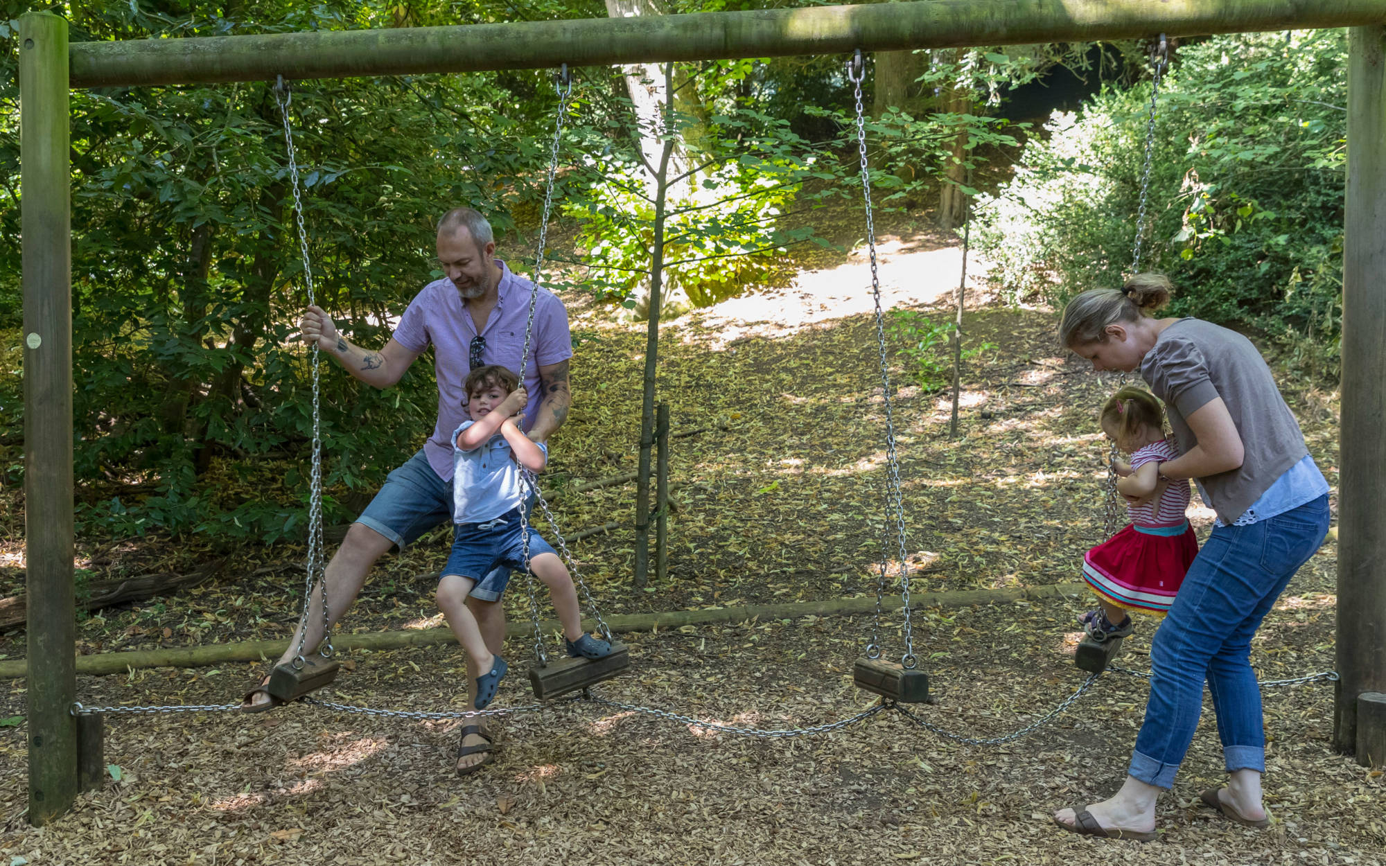 Famiy with children playing on the swings in the Woodland Playground