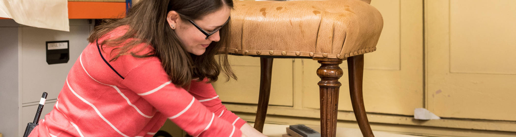 Woman polishes the legs of an antique chair