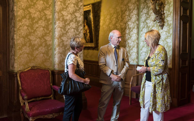 A house guide talks with two members of the public
