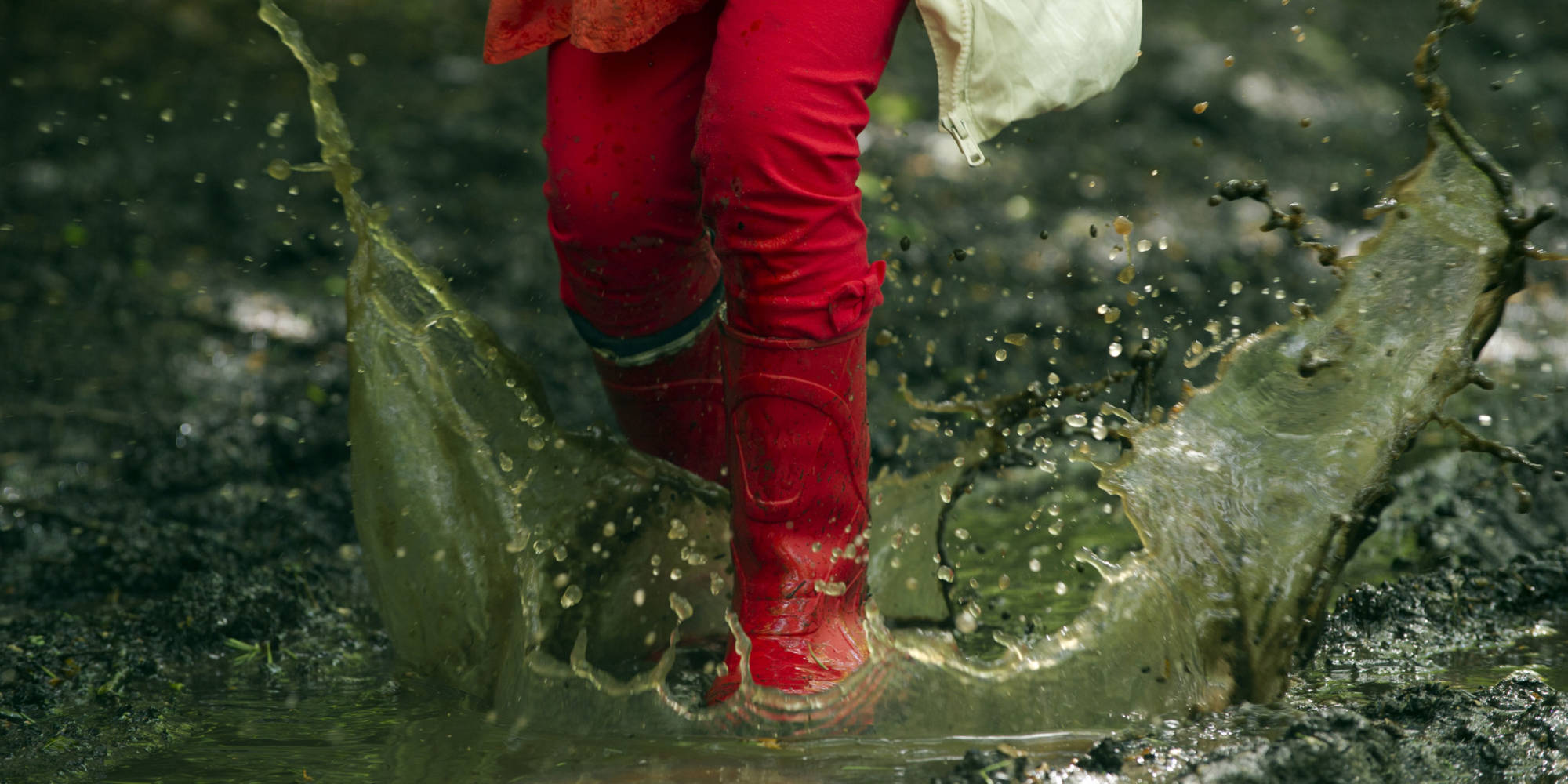 young girl splasing in a puddle