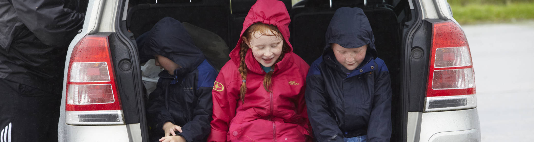 children in the back of a car sheltering from the rain