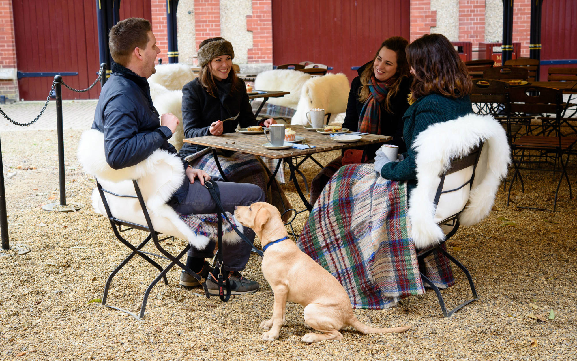 Group of friends with their dog enjoying coffee at the Stables café at Waddesdon Manor