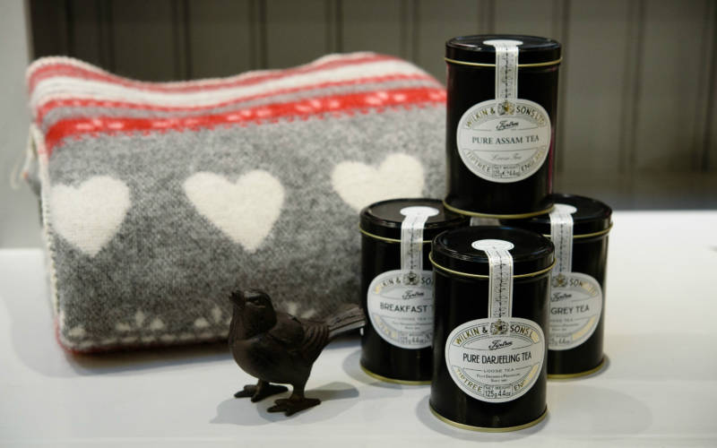Shop products such as blankets and teas are for sale in the Manor shop and Wine shop at Waddesdon during Hygge