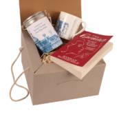 A mug, book and hot chocolate inside a gift box