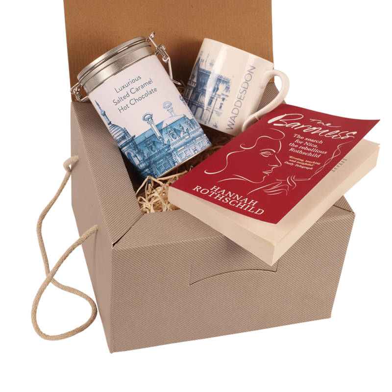 A mug, book and hot chocolate inside a gift box
