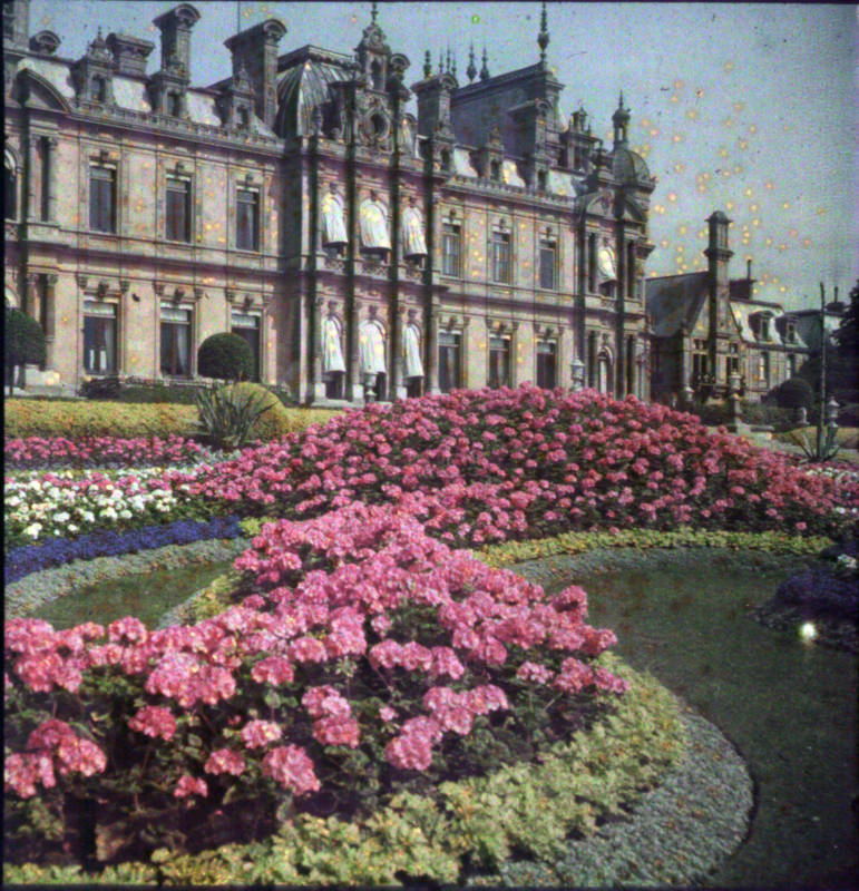 1910 auto-chrome of the colourful parterre at the south of the manor