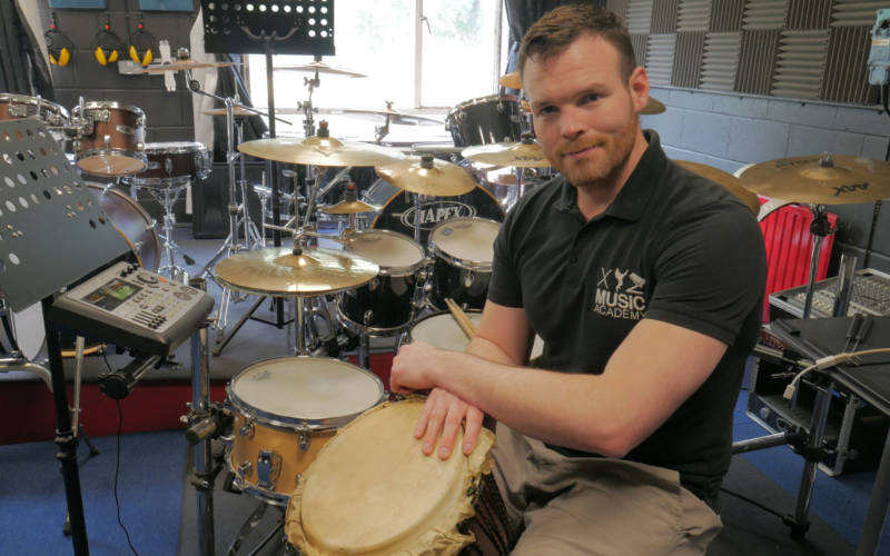 XYZ team member shown here with the vast drum kit they have to offer.