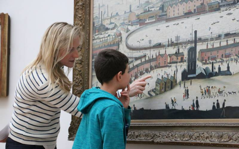 Child looking at a painting with the Little Grand Tour