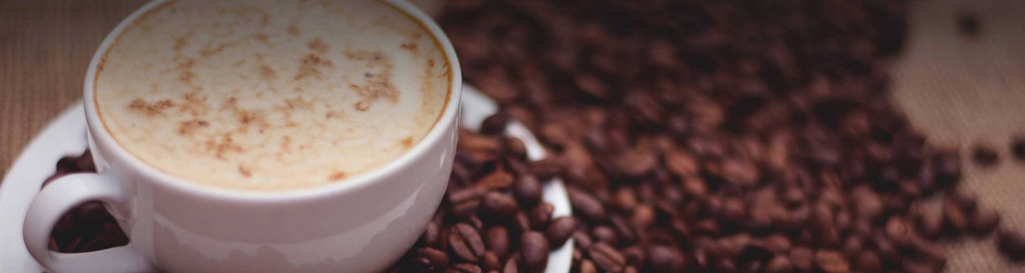 A cup of coffee with roasted beans scattered around