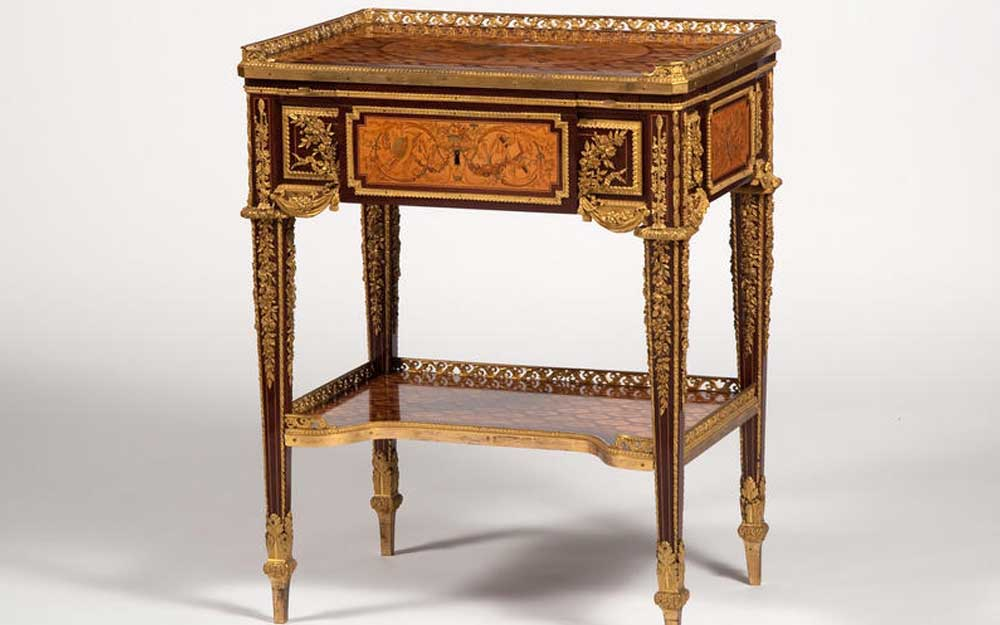Small writing table veneered with fret marquetry and five panels depicting trophies of the arts, with elaborate gilt-bronze mounts.