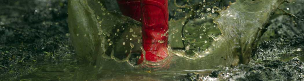 Red wellington boots splashing in a puddle