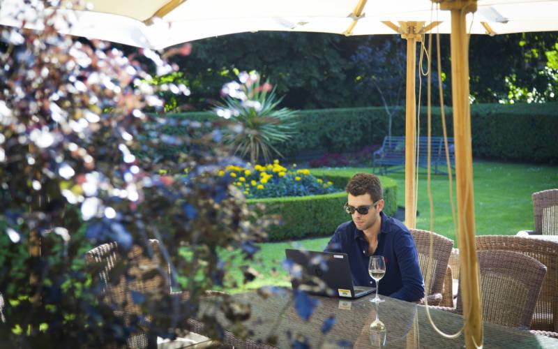 Hotel-exterior-back-summer-person-laptop-alfresco-sasa-savic-3000x1875