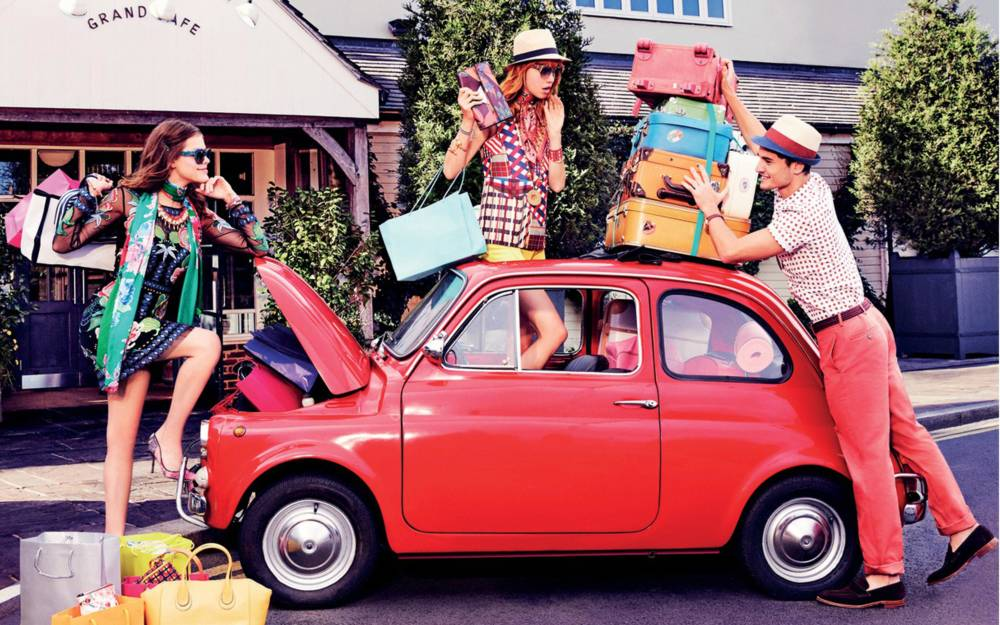 A small red car with suitcases and shopping on the roof