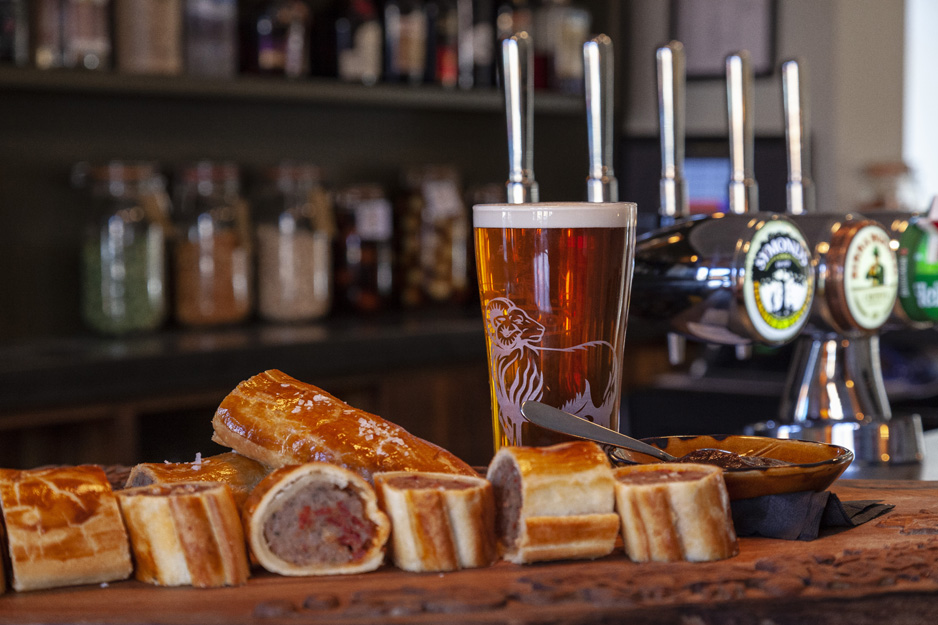 Sausage roll and beer on a bar